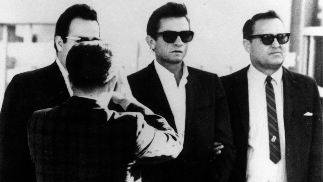 Johnny Cash is flanked by a bondsman and a US Marshall as he was transferred from El Paso County Jail to the Federal Courthouse Oct. 5, 1965.