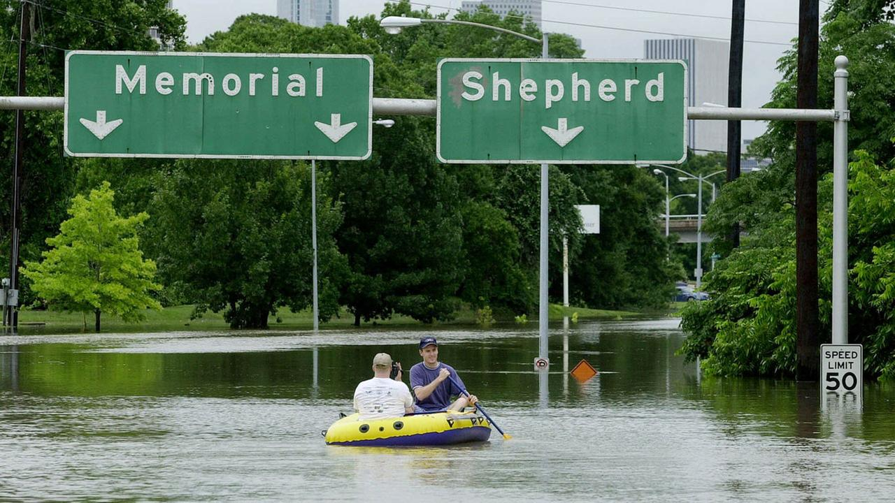 FILE - Bryan Christiansen, right, and his cousin, Read Flake, paddle a rubber raft down Memorial Drive near downtown Houston on Saturday afternoon, June 9, 2001.