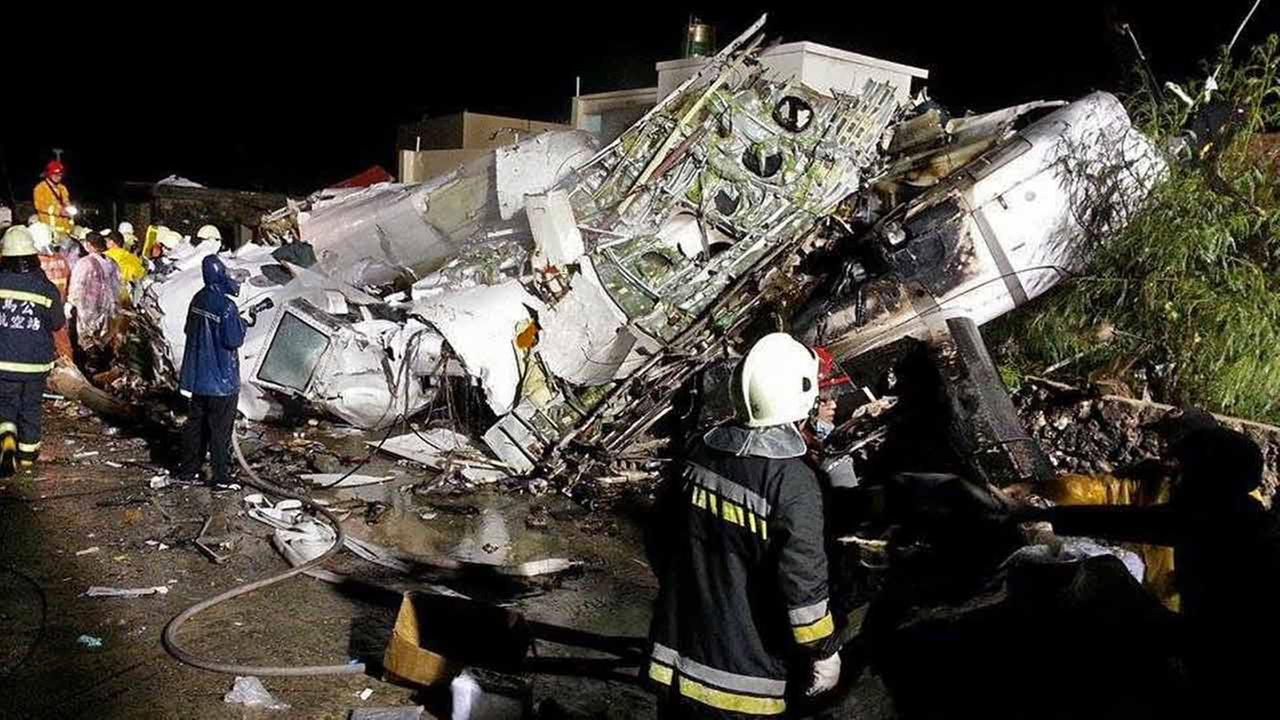 Rescue workers survey the wreckage of TransAsia Airways flight GE222 which crashed while attempting to land in stormy weather on the Taiwanese island of Penghu.