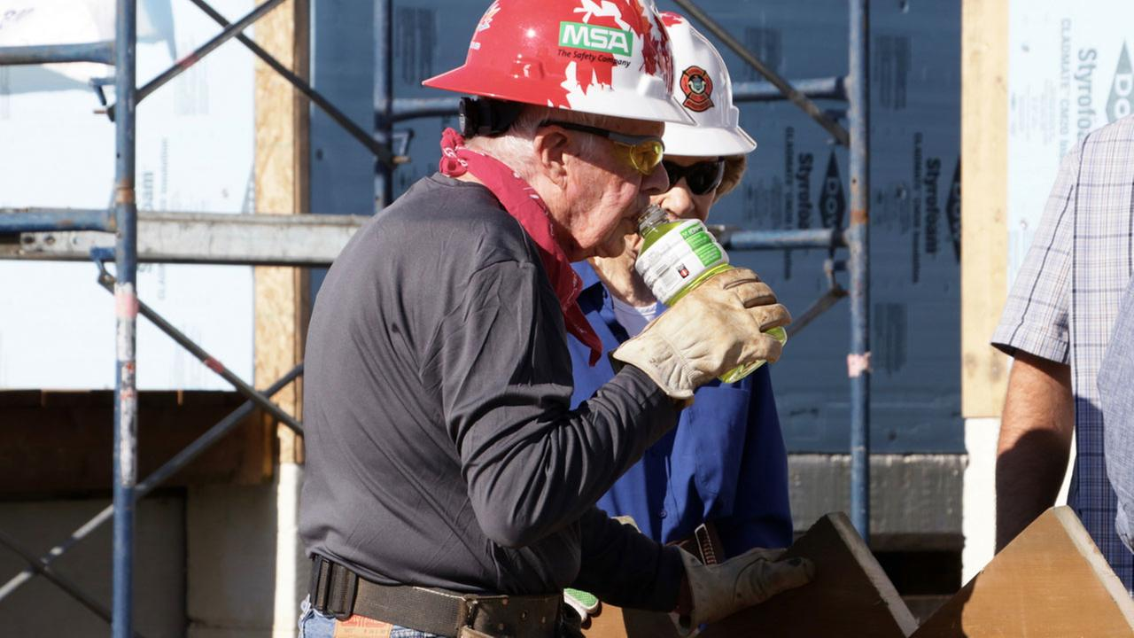 Former U.S. President Jimmy Carter drinks while helping build homes for Habitat for Humanity in Winnipeg, Manitoba on Thursday, July 13, 2017.