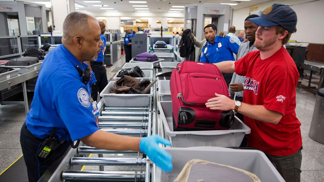 A TSA official helps passengers load their carry-on belongings onto an automated conveyer belt at a newly designed passenger screening lane.