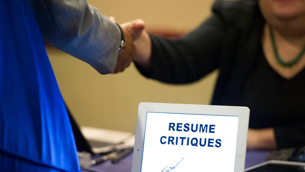 FILE - In this Thursday, May 30, 2013, file photo, a job seeker stops at a table offering resume critiques during a job fair held in Atlanta.