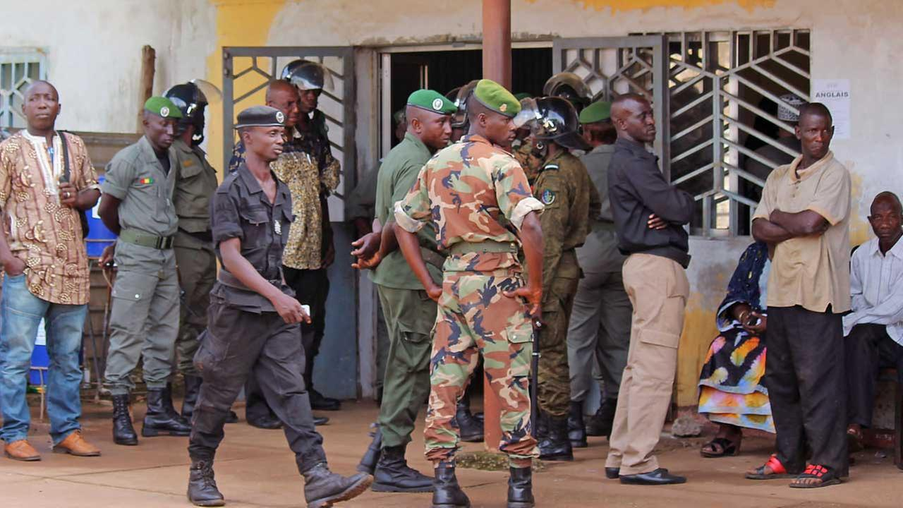 Guinea troops, center, provide security at the entrance to the morgue were the victims of a stampede that took place the night before at a rap concert.