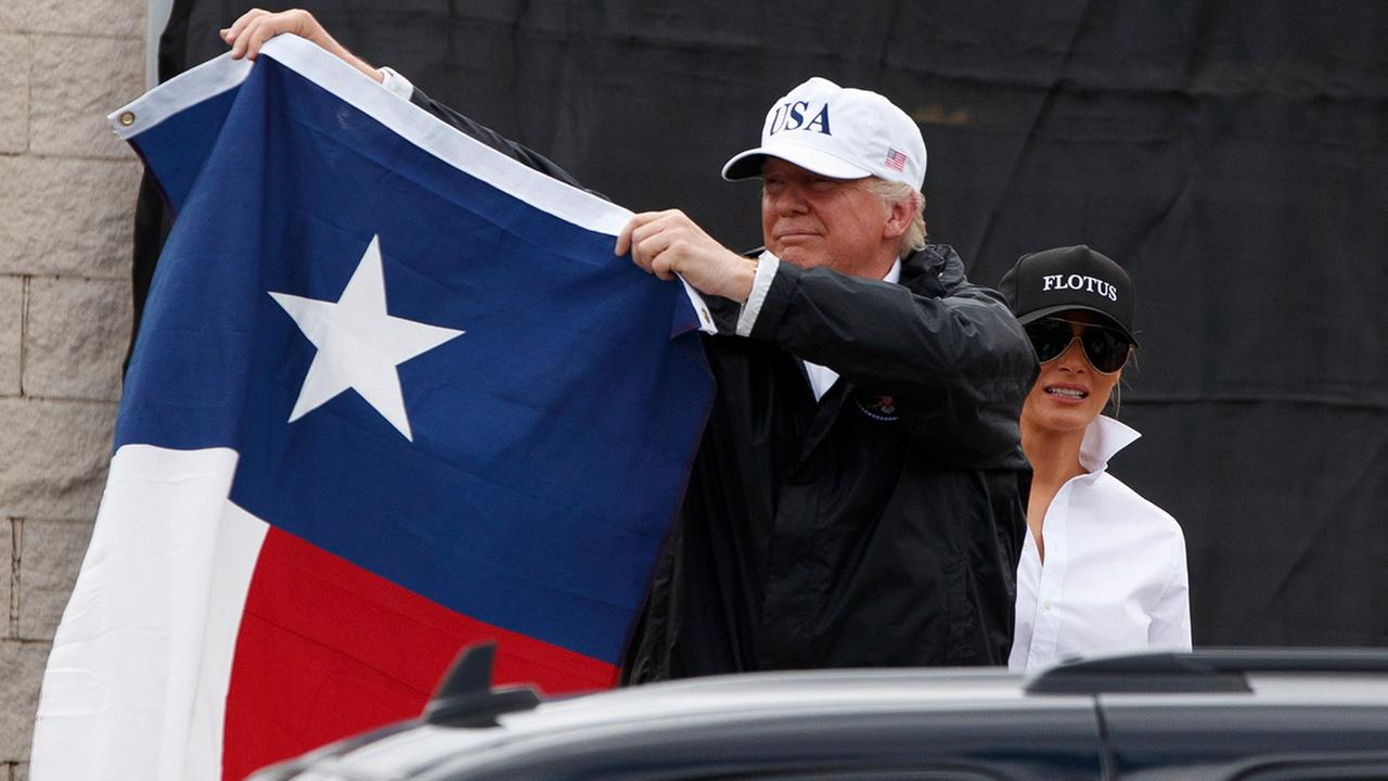 President Donald Trump, accompanied by first lady Melania Trump, holds up a Texas flag after speaking with supporters outside Firehouse 5 in Corpus Christi, Texas, Aug. 29, 2017.