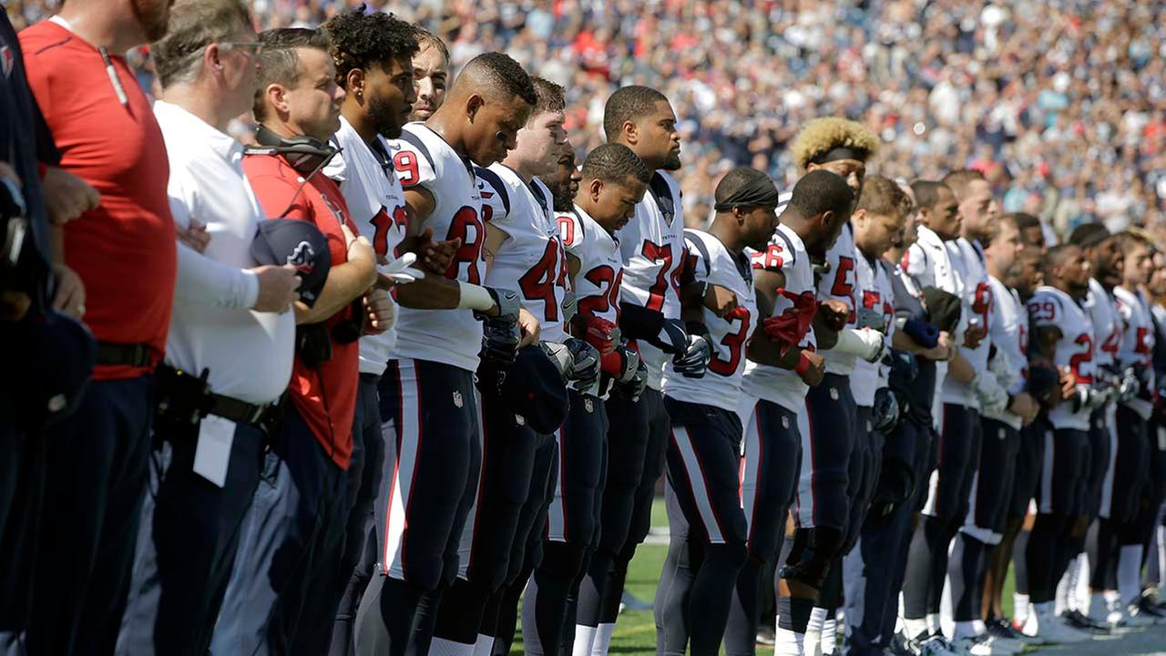 Members of the Houston Texans team stand with arms locked during the national anthem before an NFL football game against the New England Patriots.