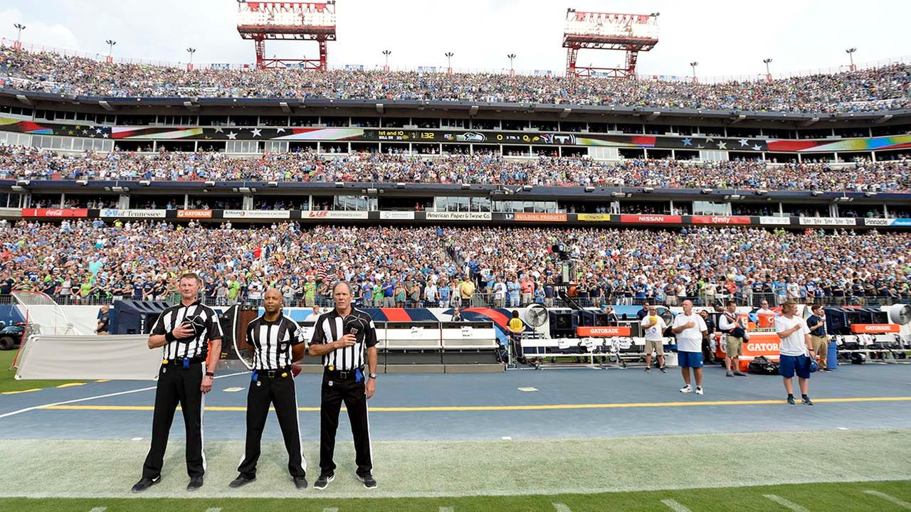 Officials stand on the sideline of the Seattle Seahawks during the playing of the national anthem before an NFL football game between the Seahawks and the Tennessee Titans.