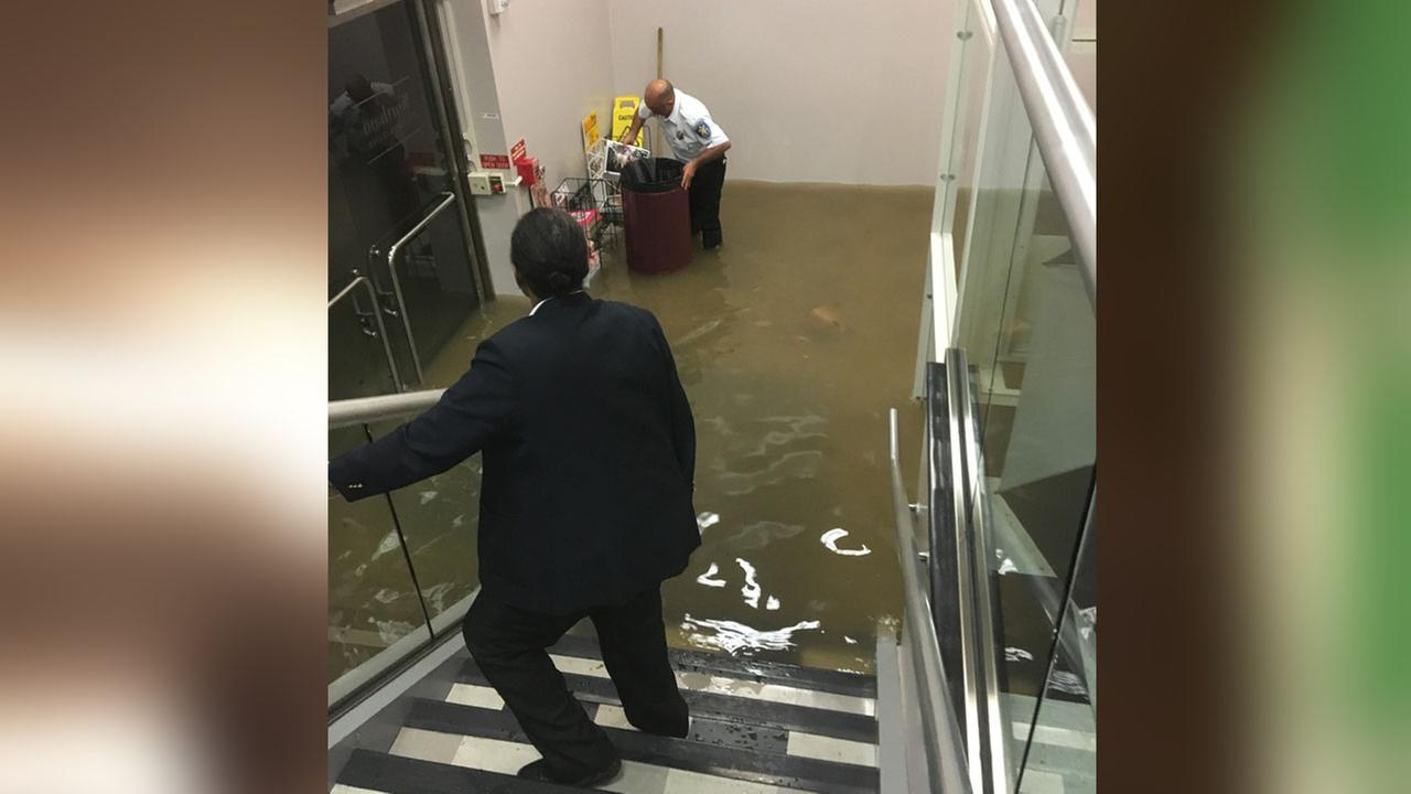 A Wortham Center employee puts magazines and newspapers into a trash can as water floods the entrance.