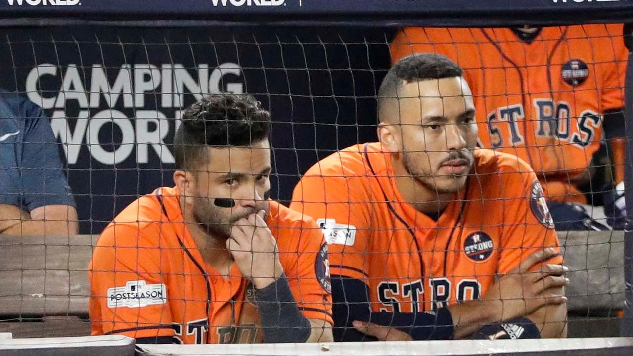 Houston Astros Jose Altuve and Carlos Correa watch from the dugout during the seventh inning of Game 5, in New York. (AP Photo/David J. Phillip)