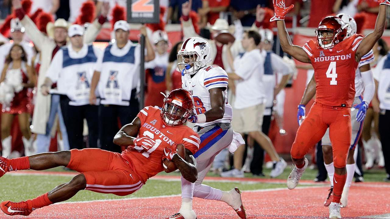 Houston Cougars wide receiver Ellis Jefferson (21) falls into the end zone to score as SMU defensive back Christian Davis (28) defends as DEriq King celebrates in the first half.