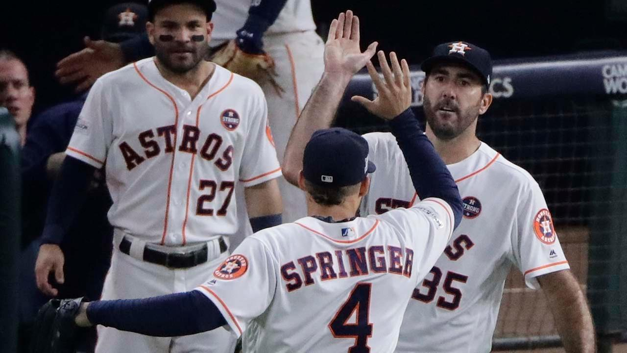 Houston Astros Justin Verlander congratulates George Springer (4) after a catch at the wall of a ball hit by New York Yankees Todd Frazier during the seventh inning.