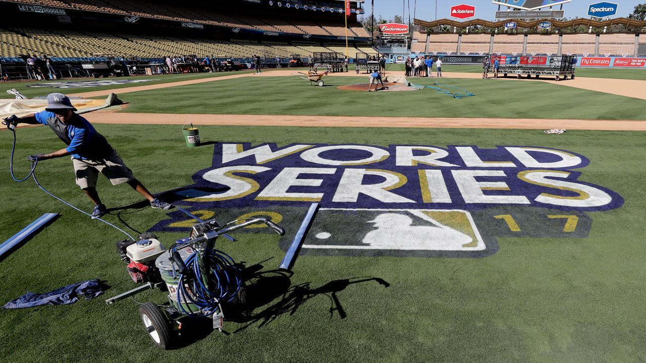 Oscar Del Real paints the World Series logo on the field at Dodgers Stadium before media day for baseballs World Series between the Houston Astros and the Los Angeles Dodgers.
