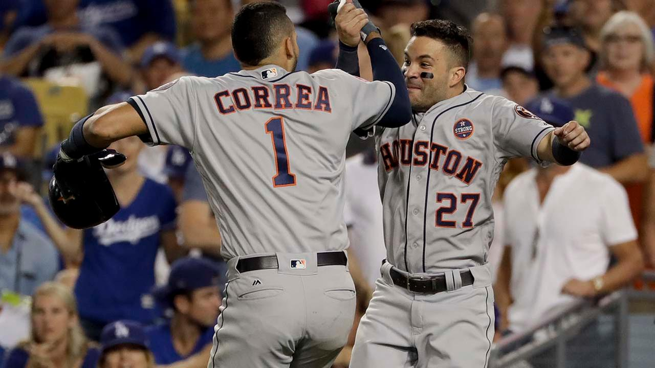Houston Astros Carlos Correa, left, and Jose Altuve celebrates their back-to-back home run against the Los Angeles Dodgers during the 10th inning of Game 2. (AP Photo/Matt Slocum)