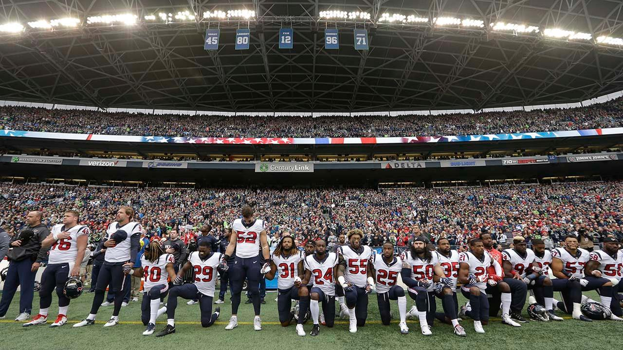 Houston Texans players kneel and stand during the singing of the national anthem before an NFL football game against the Seattle Seahawks, (AP Photo/Elaine Thompson)