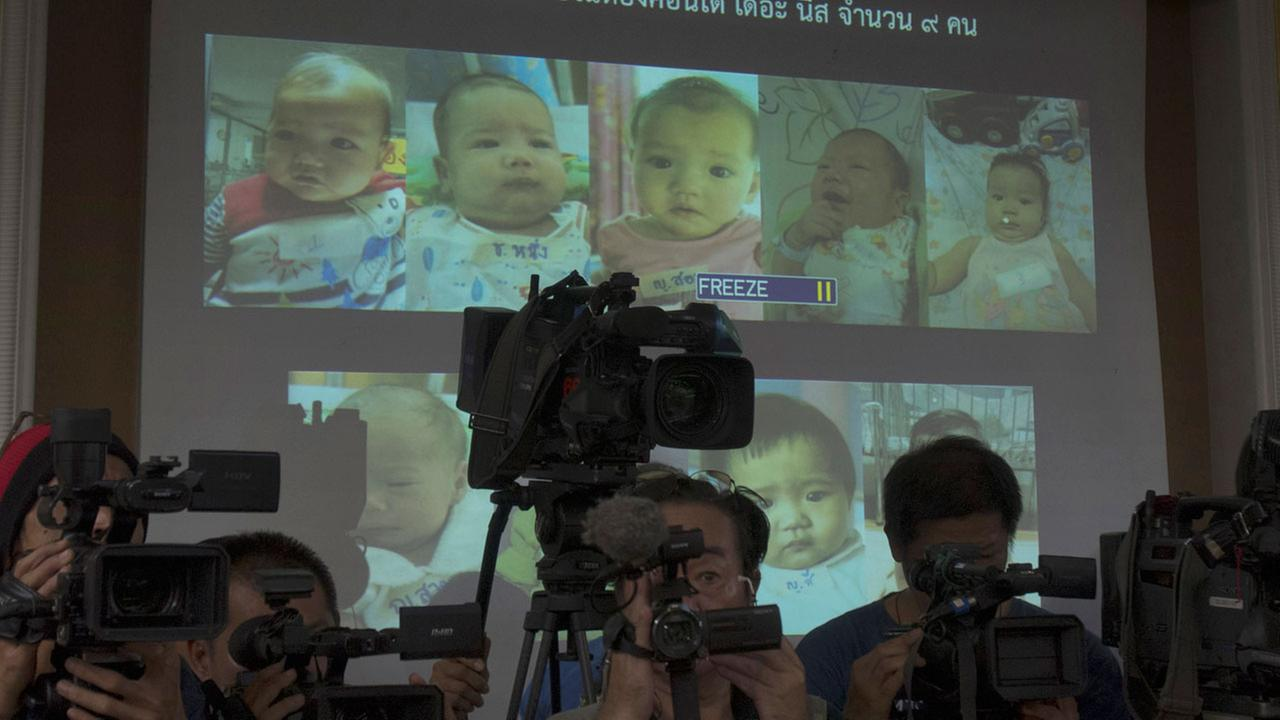Thai police display pictures of surrogate babies born to a Japanese man who is at the center of a surrogacy scandal  (AP)