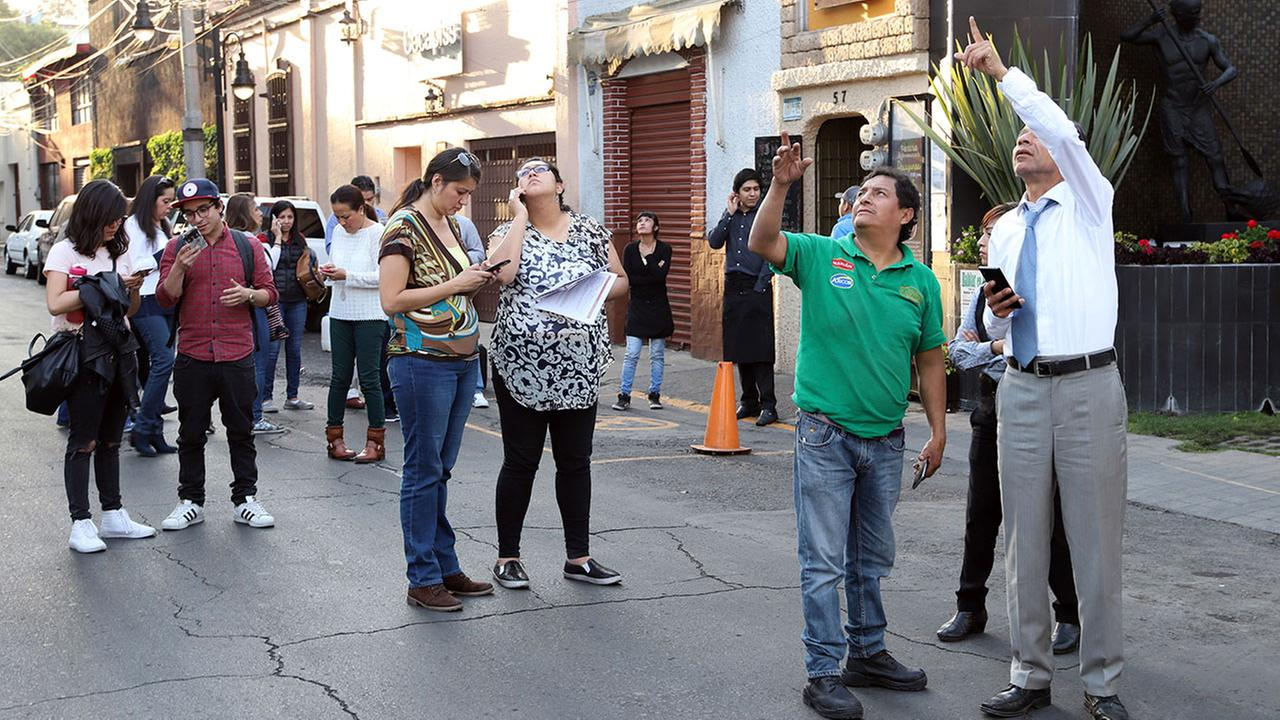 People stand in the street as an earthquake shakes Mexico City, Friday, Feb. 16, 2018. A powerful 7.2-magnitude earthquake has shaken south and central Mexico.