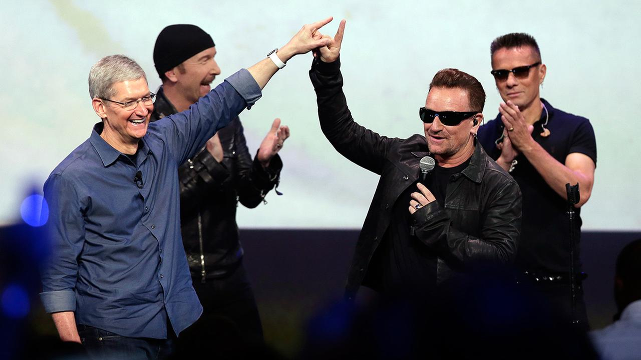 Apple CEO Tim Cook, left, greets Bono from the band U2