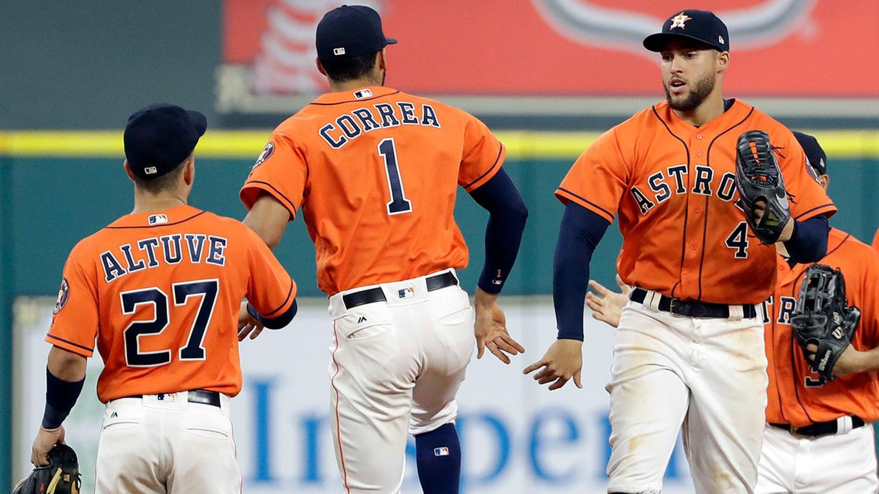 Houston Astros George Springer (4), Carlos Correa (1) and Jose Altuve (27) celebrate after beating the Oakland Athletics in a baseball game Friday, April 28, 2017, in Houston.