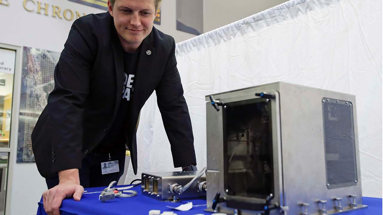 Brad Kohlenberg, a business development engineer with Made In Space, looks over a 3-D printer identical to the one that will be transported to the ISS