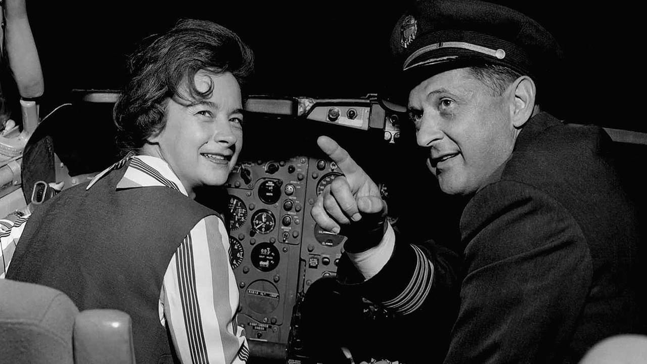 Mock, the first woman to fly solo around the world, takes a look at the controls in the cockpit of the plane that carried her back home to Columbus, OH, April 23, 1964
