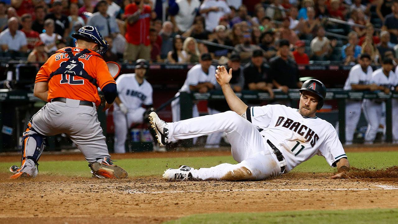Arizona Diamondbacks A.J. Pollock scores a run as Houston Astros Max Stassi chases down a wide throw at home plate on Tuesday, Aug. 15, 2017, in Phoenix.
