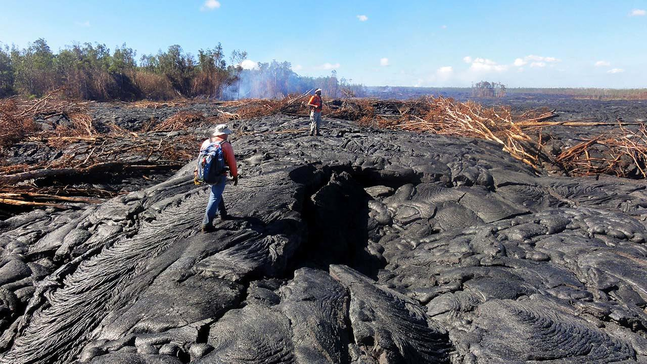 Hawaii Volcano Observatory geologists walk over the surface of the lava flow