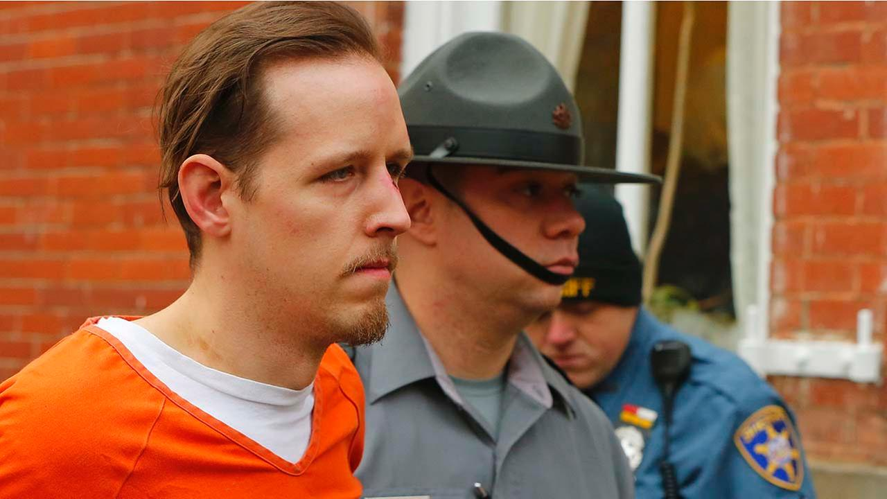 Eric Frein is escorted by police out the Pike County Courthouse after his arraignment in Milford, Pa., Friday Oct. 31, 2014