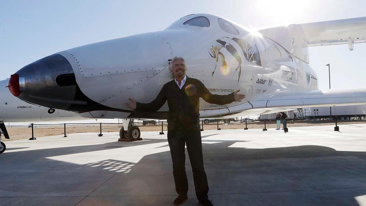 British entrepreneur Richard Branson poses with SpaceShipTwo, mounted under its mother ship White Knight at a Virgin Galactic hangar at Mojave Air and Space Port in Mojave, CA