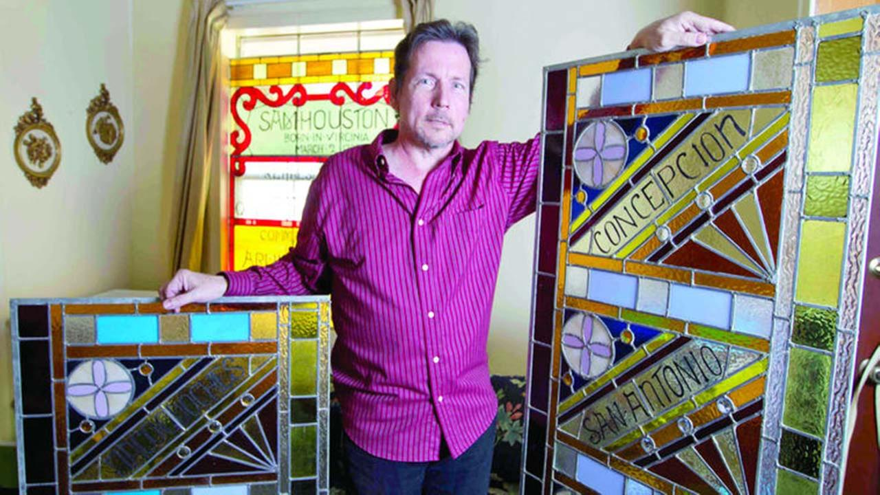 Sam Houston State University alumnus Joe Janczak poses with sections of his rebuilt 17-foot stained glass window honoring Sam Houston and Texas heroes at his home in Spring.