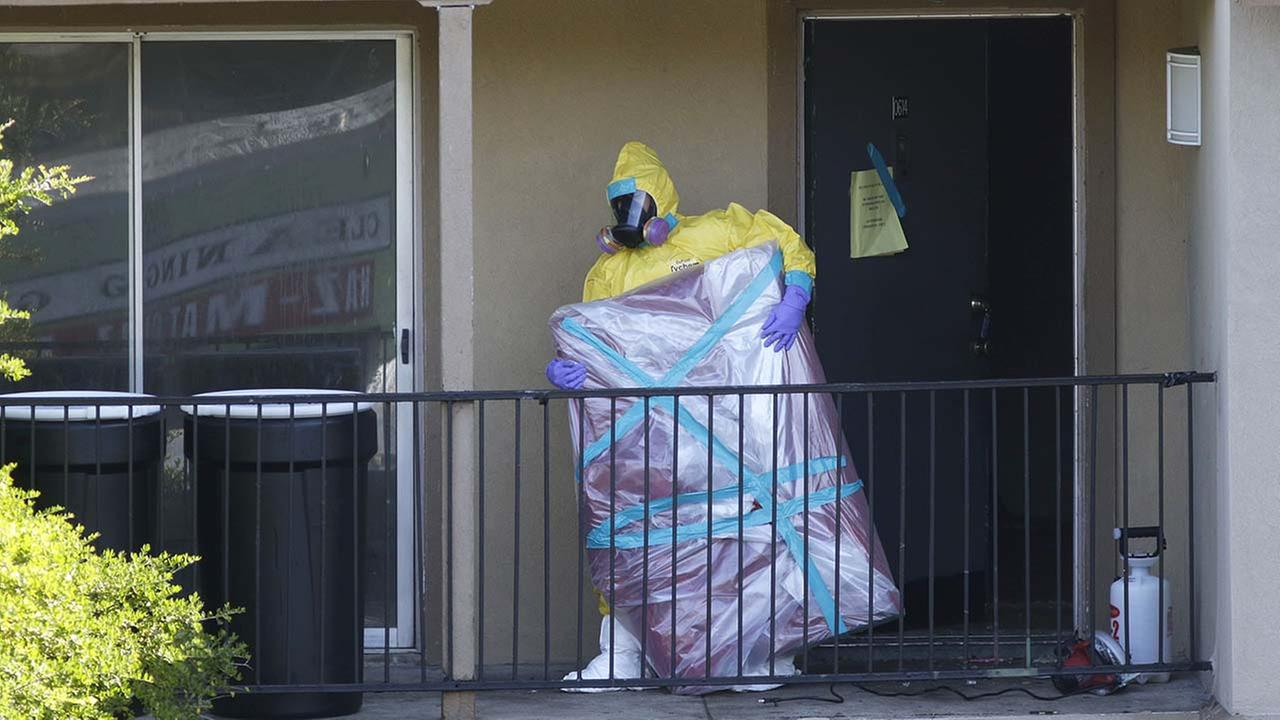 In this Oct. 6, 2014, file photo, a hazardous material cleaner removes a wrapped item from the Louise Trohs apartment where Thomas Eric Duncan stayed