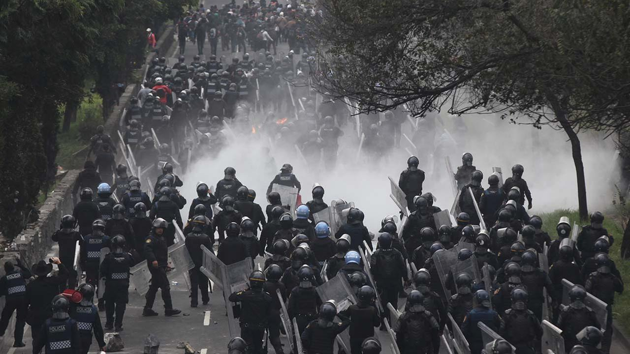 Scores of riot police march to confront protesters near the airport in Mexico City,Thursday, Nov. 20, 2014
