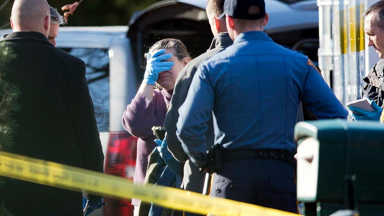 A woman speaks with investigators at the scene of a shooting Thursday, Nov. 20, 2014, in Tabernacle, N.J.