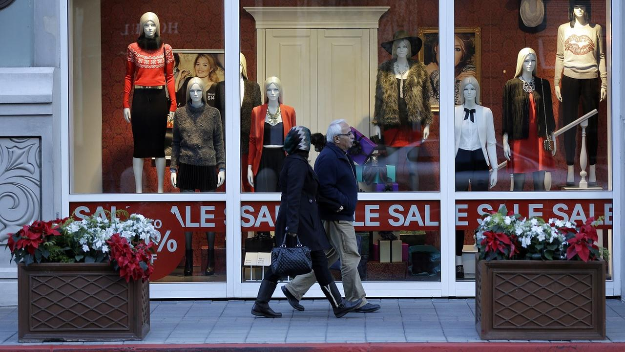 Shoppers walk in front of a store advertising a sale.