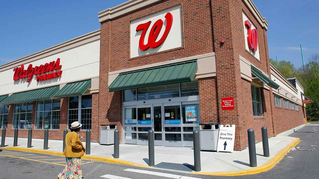In this Wednesday, May 14, 2014 file photo, a customer walks toward the entrance to a Walgreens store, in Boston.