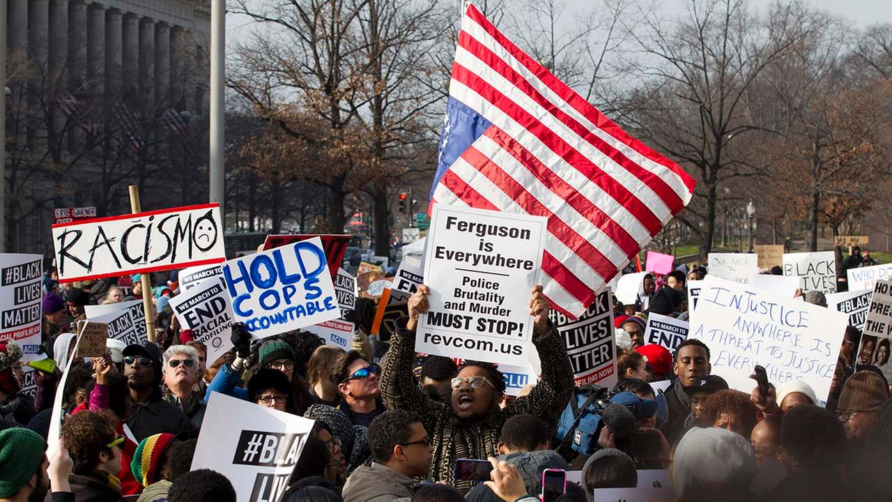 Demonstrators chant at Freedom Plaza in Washington, Saturday, Dec. 13, 2014, during the Justice for All rally and march