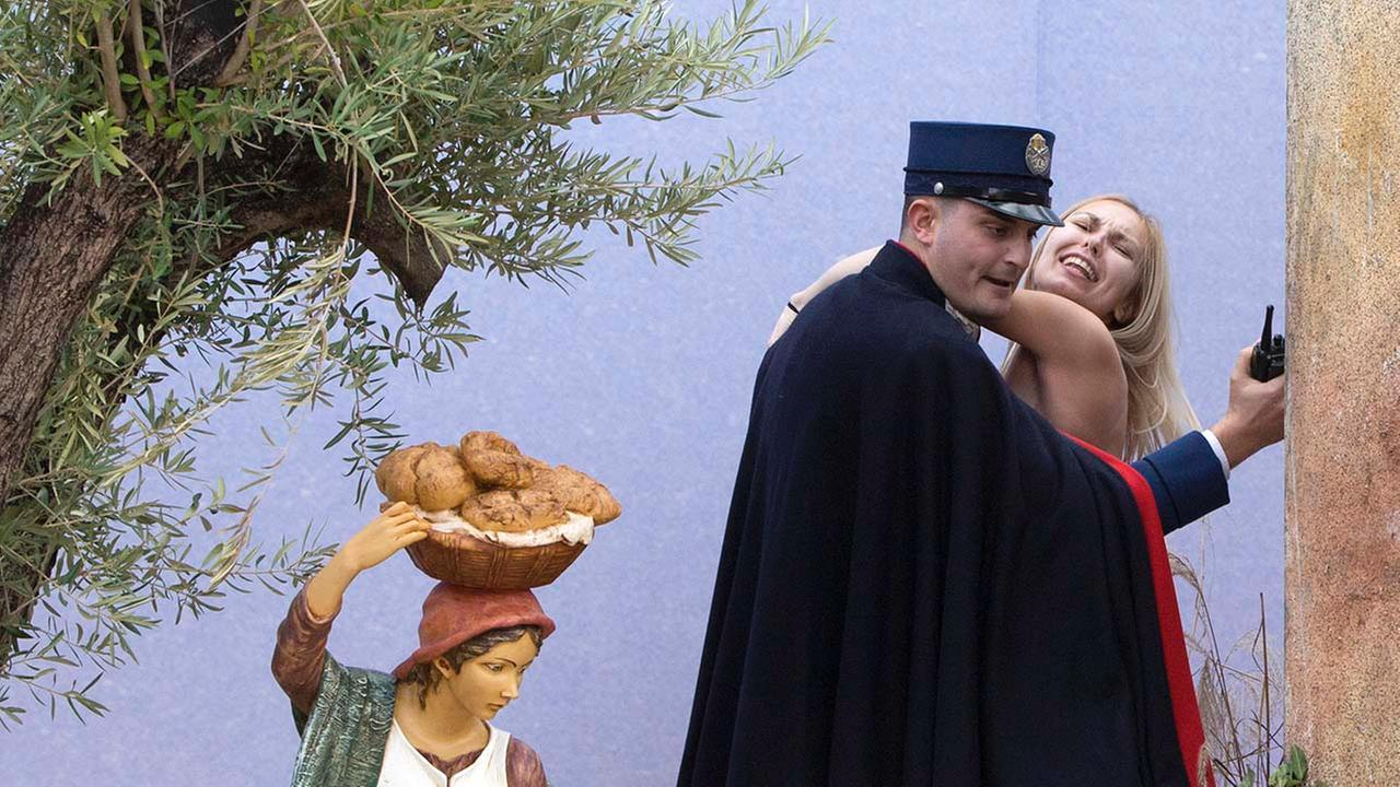 A gendarme from the Vaticans security forces stops a Ukrainian feminist group Femen activist after she snatched the statue of Baby Jesus