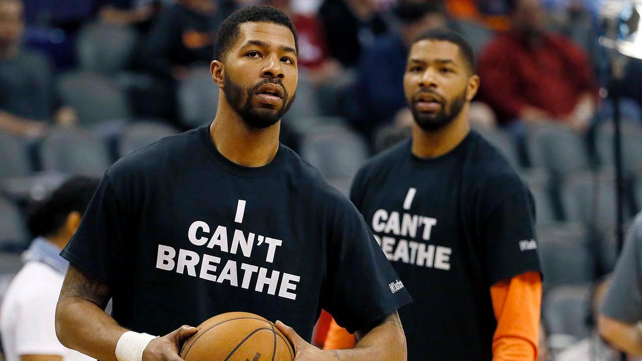 Phoenix Suns Markieff Morris, left, and his brother, Marcus Morris, warm up prior to an NBA basketball game against the Milwaukee Bucks, Monday, Dec. 15, 2014, in Phoenix.