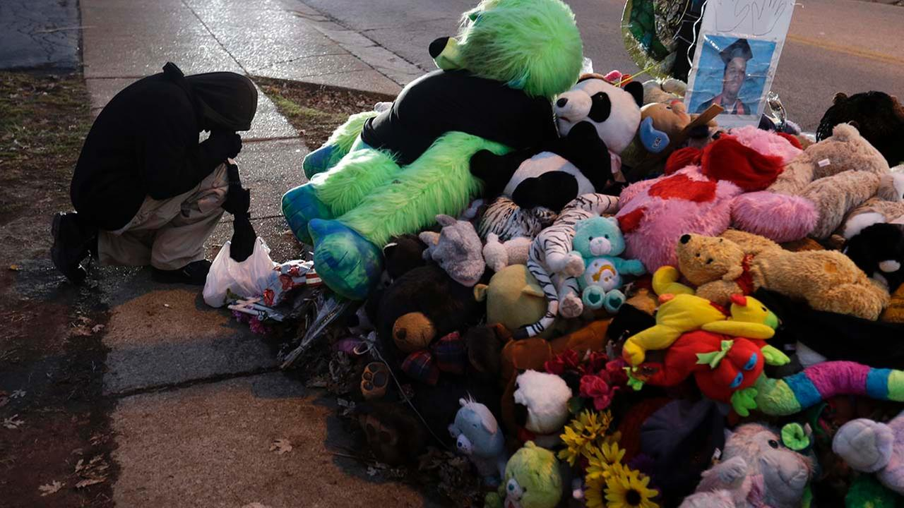 A protester kneels next to a memorial in the middle of the street, Monday, Nov. 24, 2014, more than three months after a black 18-year-old man was shot and killed there