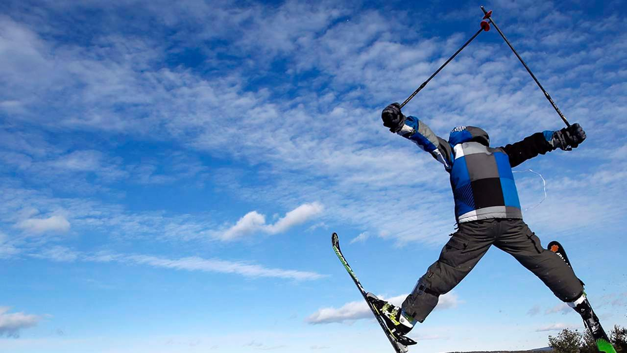 A skier catches some air at the Shawnee Peak ski resort, where man-made snow made for good holiday skiing, Monday, Dec. 29, 2014, in Bridgton, Maine
