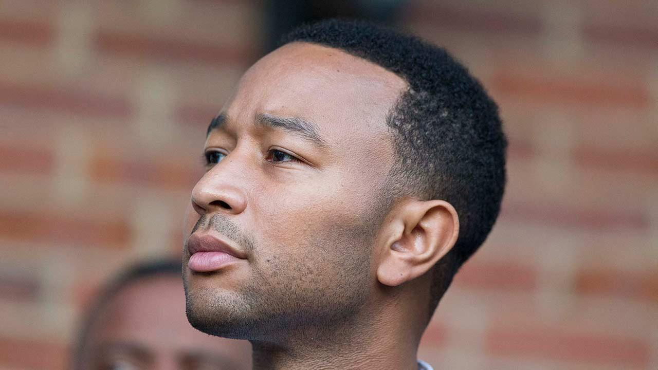 Singer and song writer John Legend listens to the speakers before he makes his way to the Edmund Pettus Bridge in honor of Martin Luther King Jr.,Sunday, Jan. 18, 2015.