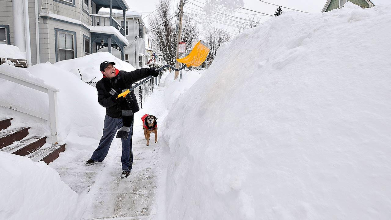 Lee Anderson adds to the pile of snow beside the sidewalk in front of his house in Somerville, Mass., Tuesday, Feb. 10, 2015, as his dog Ace looks on.