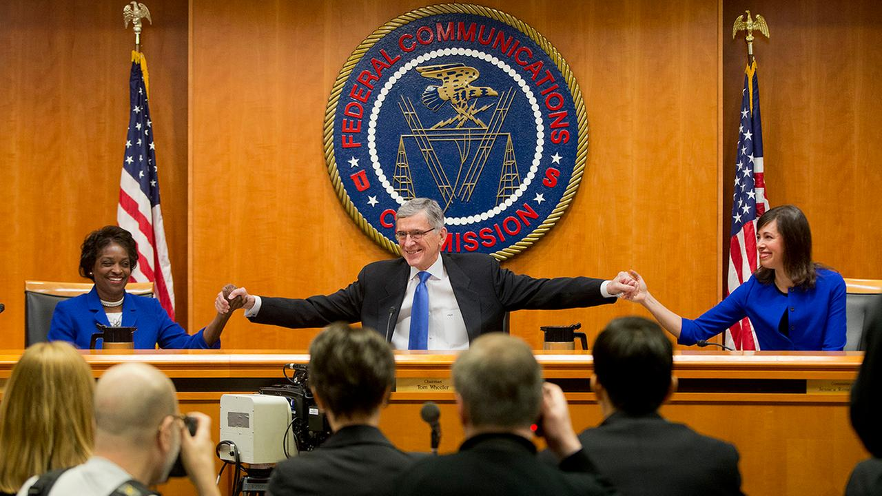 Federal Communication Commission (FCC) ChairmanTom Wheeler, center, joins hands with FCC Commissioners Mignon Clyburn, left, and Jessica Rosenworcel