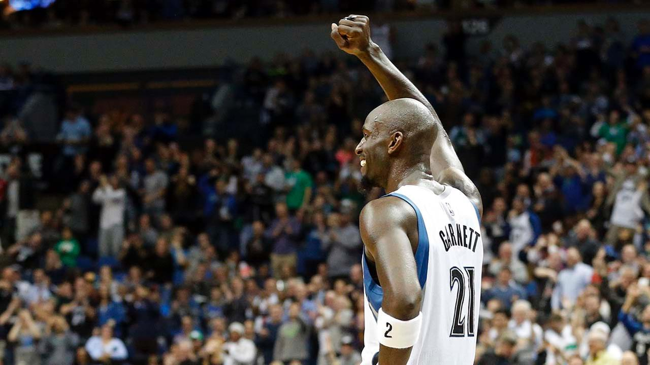 Minnesota Timberwolves Kevin Garnett acknowledges a dancing fan who had Welcome Home KG written on his chest in the second half of an NBA basketball game