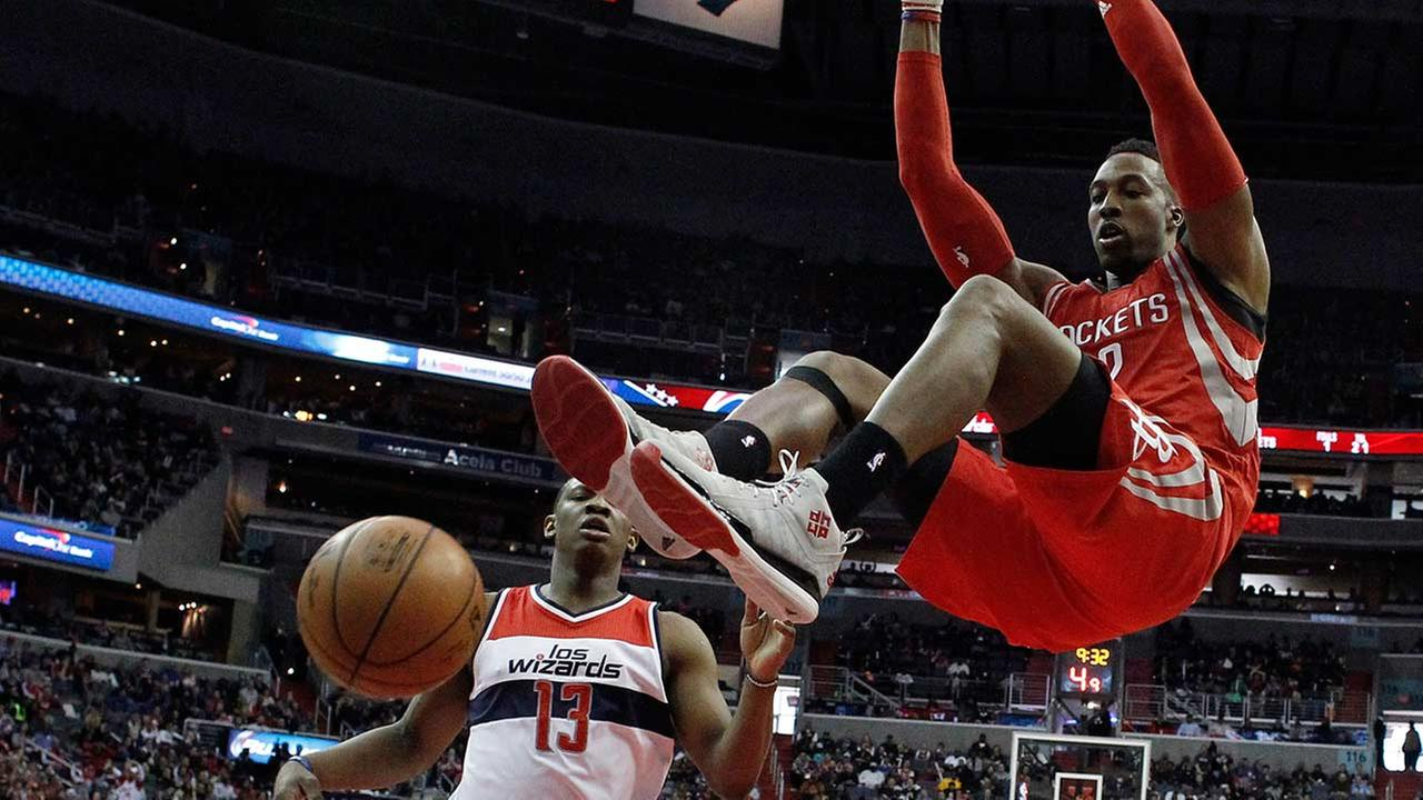 Houston Rockets center Dwight Howard, right, hangs from the rim after dunking the ball in front of Washington Wizards center Kevin Seraphin (13), from France, in the second half.