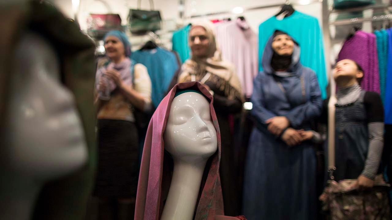 Women wearing the Islamic headscarf stand behind a mannequin in Moscow, Russia