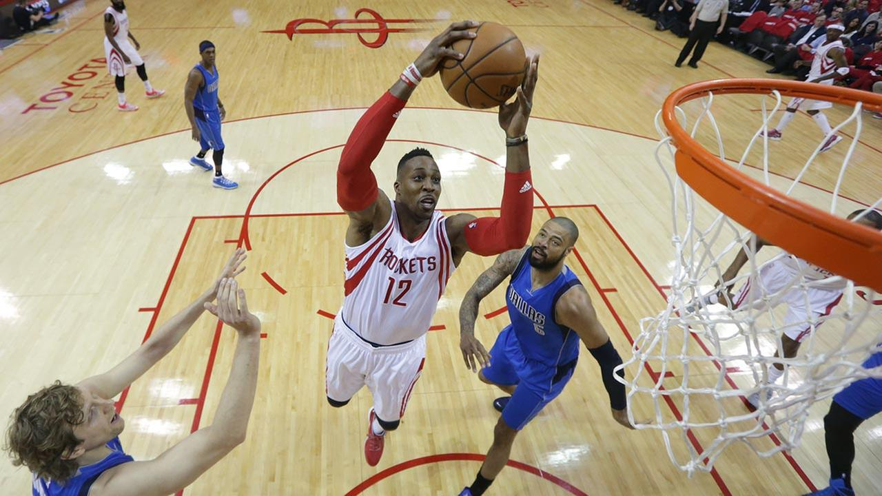 Houston Rockets Dwight Howard (12) drives to the basket between Dallas Mavericks Dirk Nowitzki, left, and Dallas Mavericks Tyson Chandler