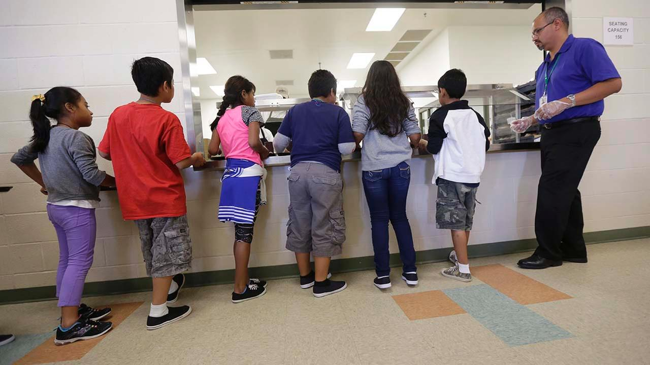 Detained immigrant children line up in the cafeteria at the Karnes County Residential Center, a temporary home for immigrant women and children detained at the border