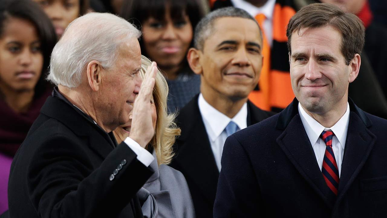 President Barack Obama, center and Beau Biden, right, watch as his father Joe Biden is sworn in, Monday, Jan. 21, 2013