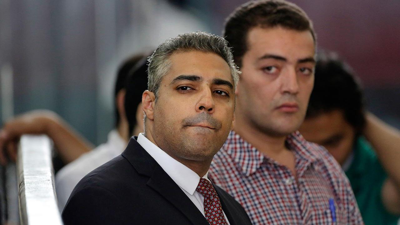 Canadian Al-Jazeera English journalist Mohammed Fahmy, left, and his Egyptian colleague Baher Mohammed listen in a courtroom in Tora prison in Cairo, Egypt