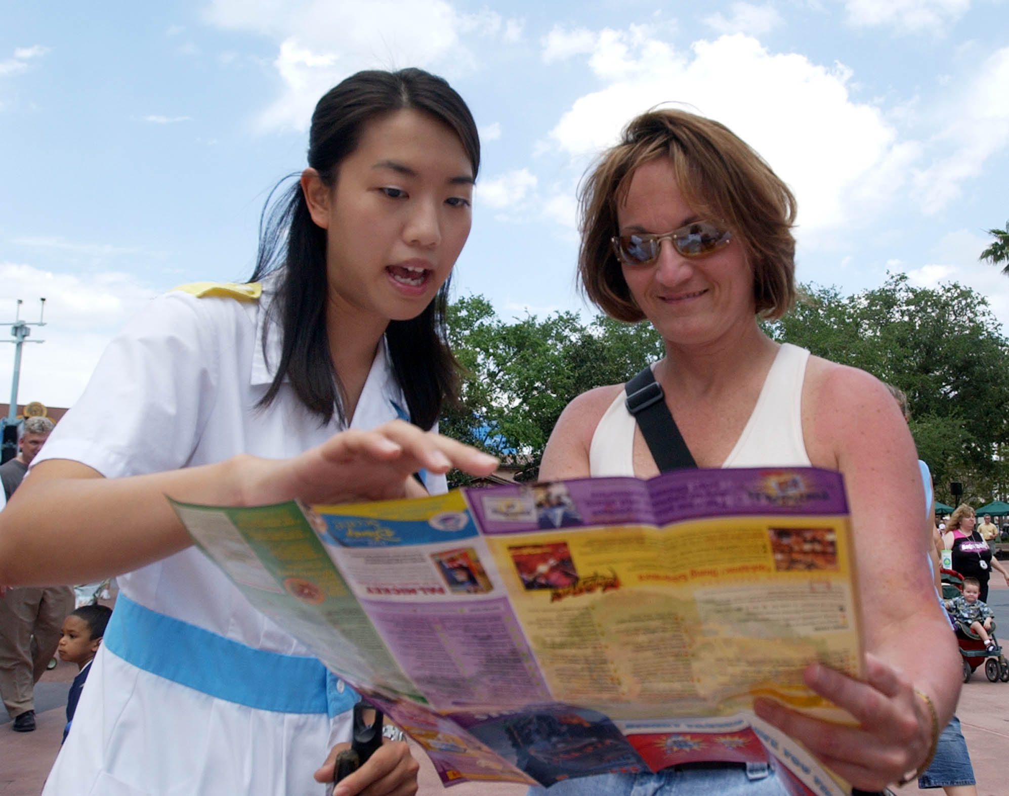 <div class='meta'><div class='origin-logo' data-origin='none'></div><span class='caption-text' data-credit='AP Photo/Peter Cosgrove'>Virginia Li, of Hong Kong, left, assists Epcot guest Gloria DeRonne, with directions at the park in Lake Buena Vista, Fla. Monday, April 12, 2005.</span></div>