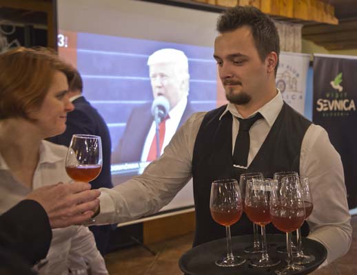 """<div class=""""meta image-caption""""><div class=""""origin-logo origin-image none""""><span>none</span></div><span class=""""caption-text"""">A waiter delivers drinks to guests as they watch a televised broadcast of the inauguration of Donald Trump at a restaurant in Sevnica, Slovenia.  (AP Photo/Darko Bandic) (AP)</span></div>"""